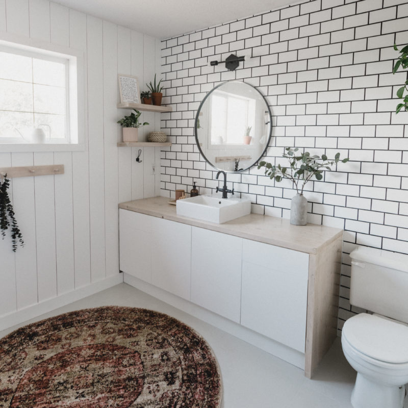 tiled bathroom with shiplap and white floors