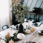 Thanksgiving tablescape with black plates, wood accents and gold cutlery