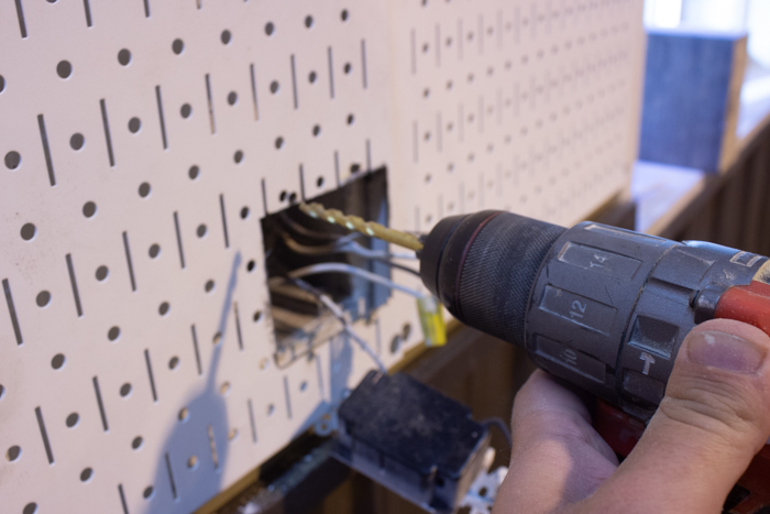 drilling an outlet into metal pegboard