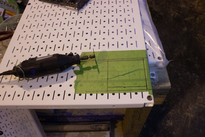 cutting a metal pegboard for installation of an outlet