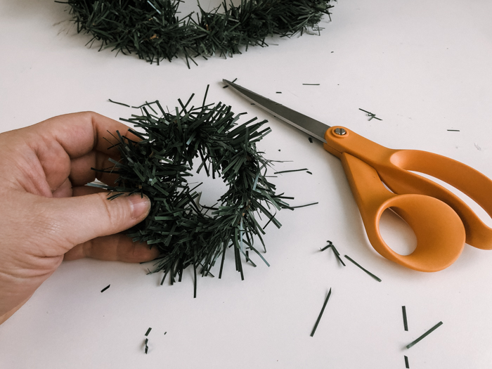 cutting the edges off of a dollar store wreath