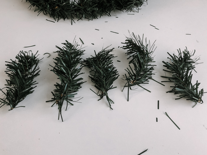 cutting pieces of faux pine wreath