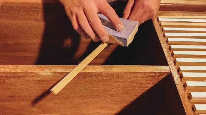 Sanding edges of slatted sideboard