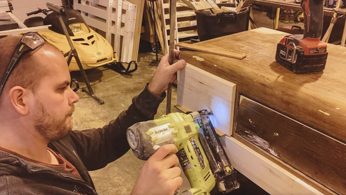 Using a nail gun to add new door fronts