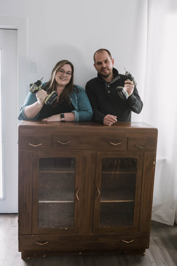 couple standing behind old thrifted cabinet for a makeover