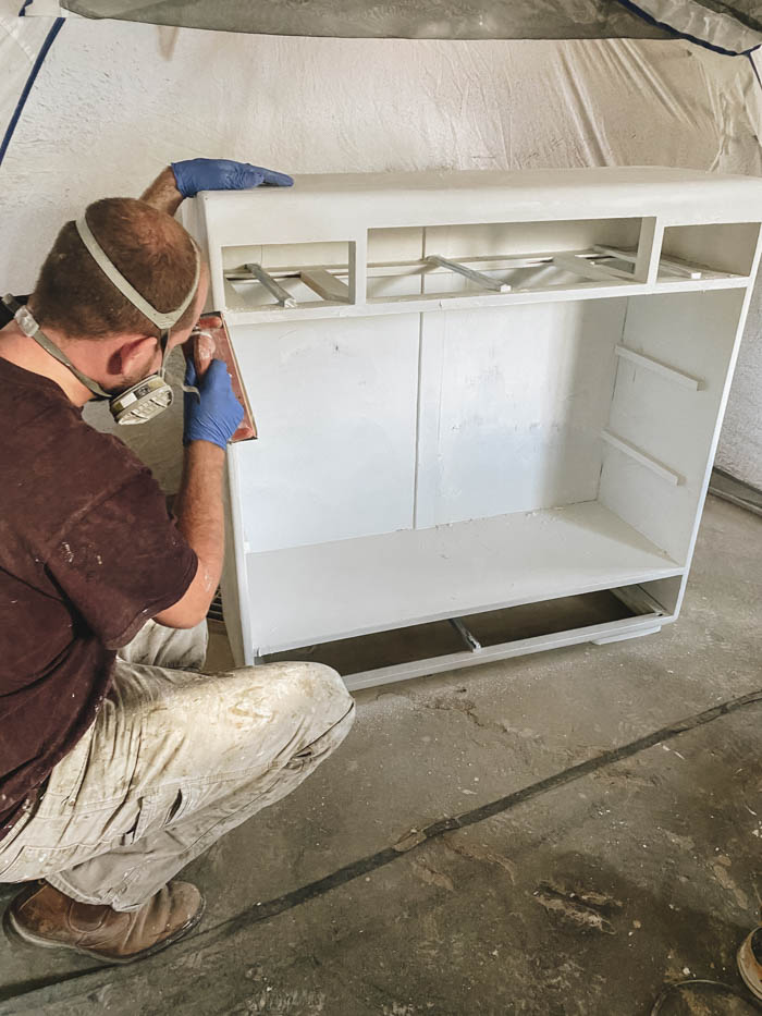 painting an old cabinet with a paint sprayer