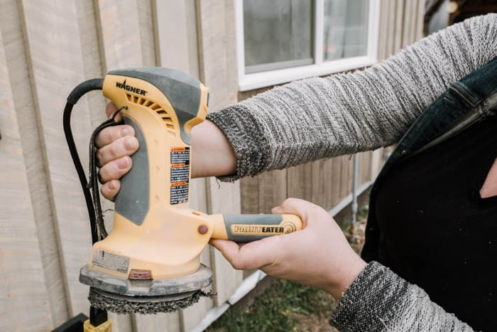 holding a painteater for sanding wood siding