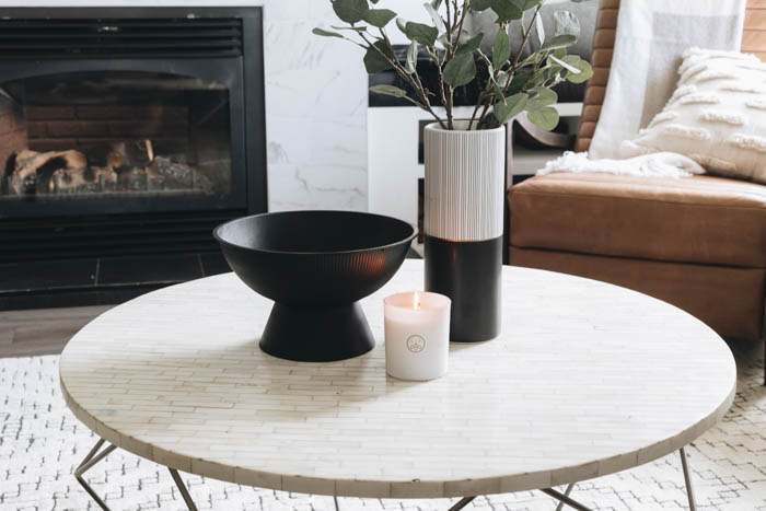 coffee table styling with a candle, vase, and bowl