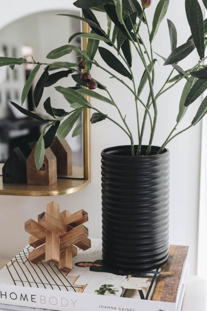 close up of black painted dollar store vase with greenery sitting on stack of books