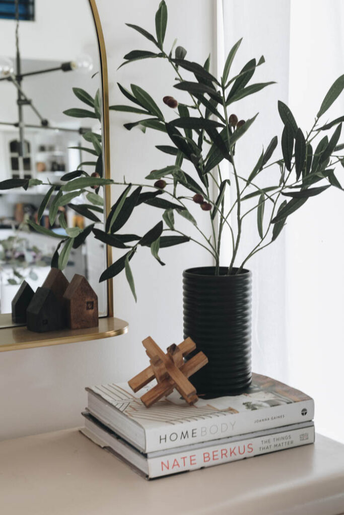 black painted dollar store vase with greenery sitting on stack of books