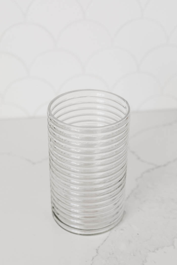 clear glass dollar store vase sitting on white counter