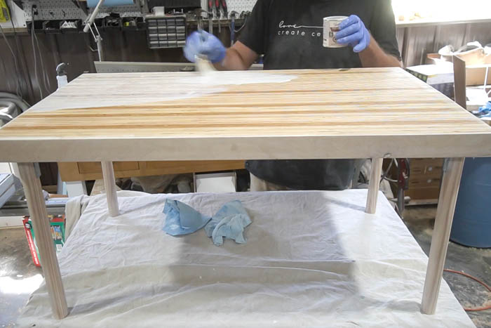 applying wood conditioner to top of table