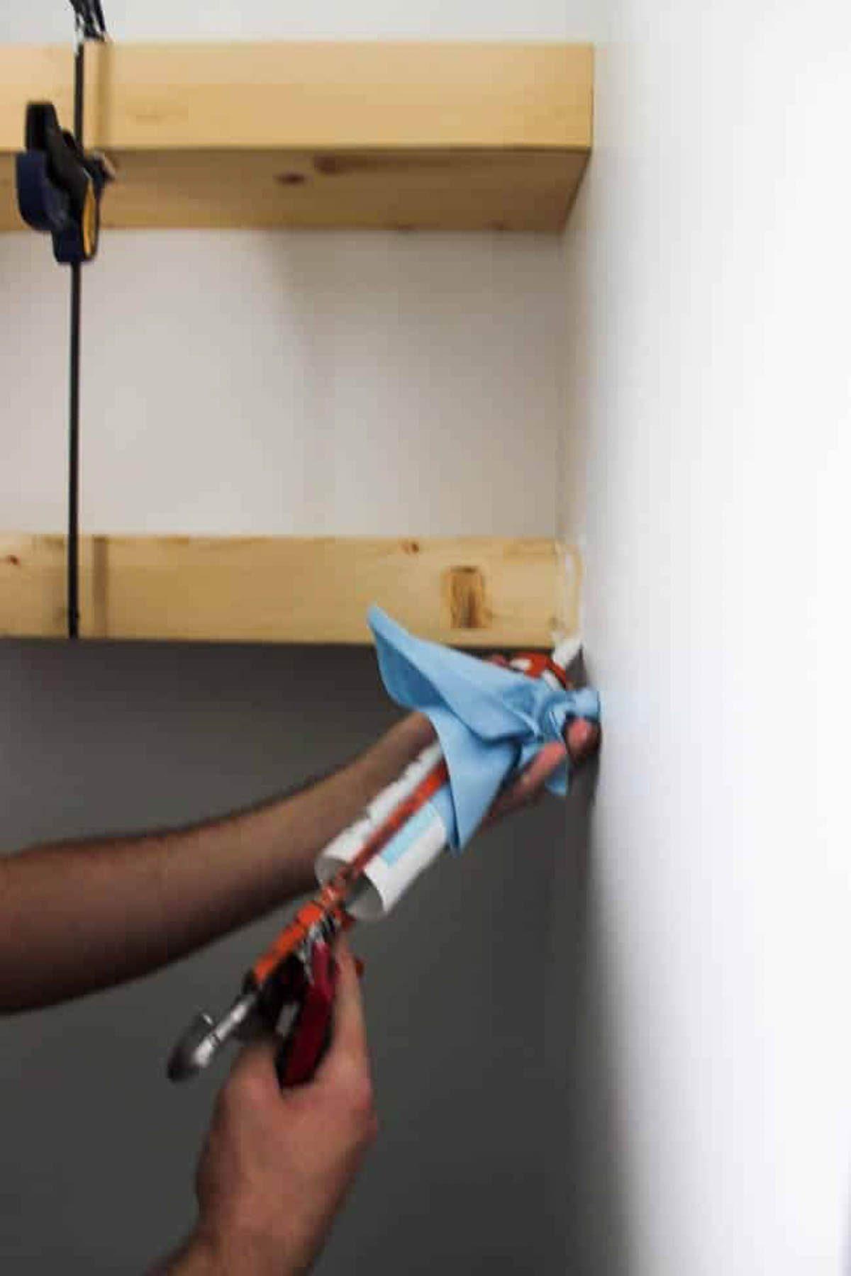 Applying caulk to edges of floating shelves