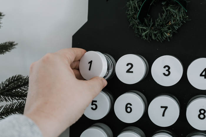 unscrewing the lid from the container on the DIY advent calendar