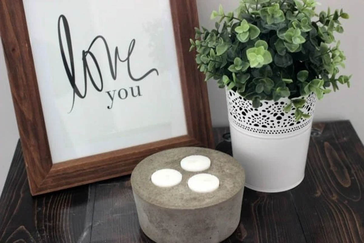 Concrete candle holder on table with plant and picture