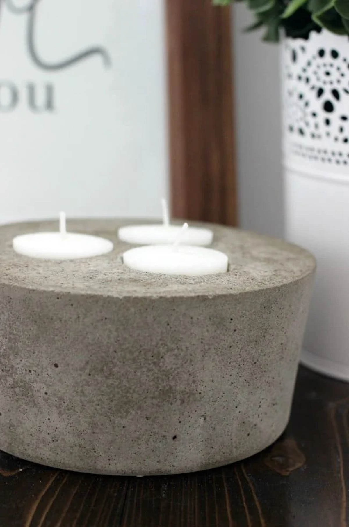 Close up image of 3 tea lights in concrete candle
