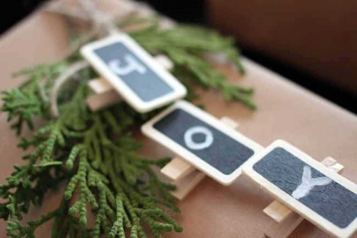 Close up of a joy sign made of clothespins on rustic wrapping paper and greenery