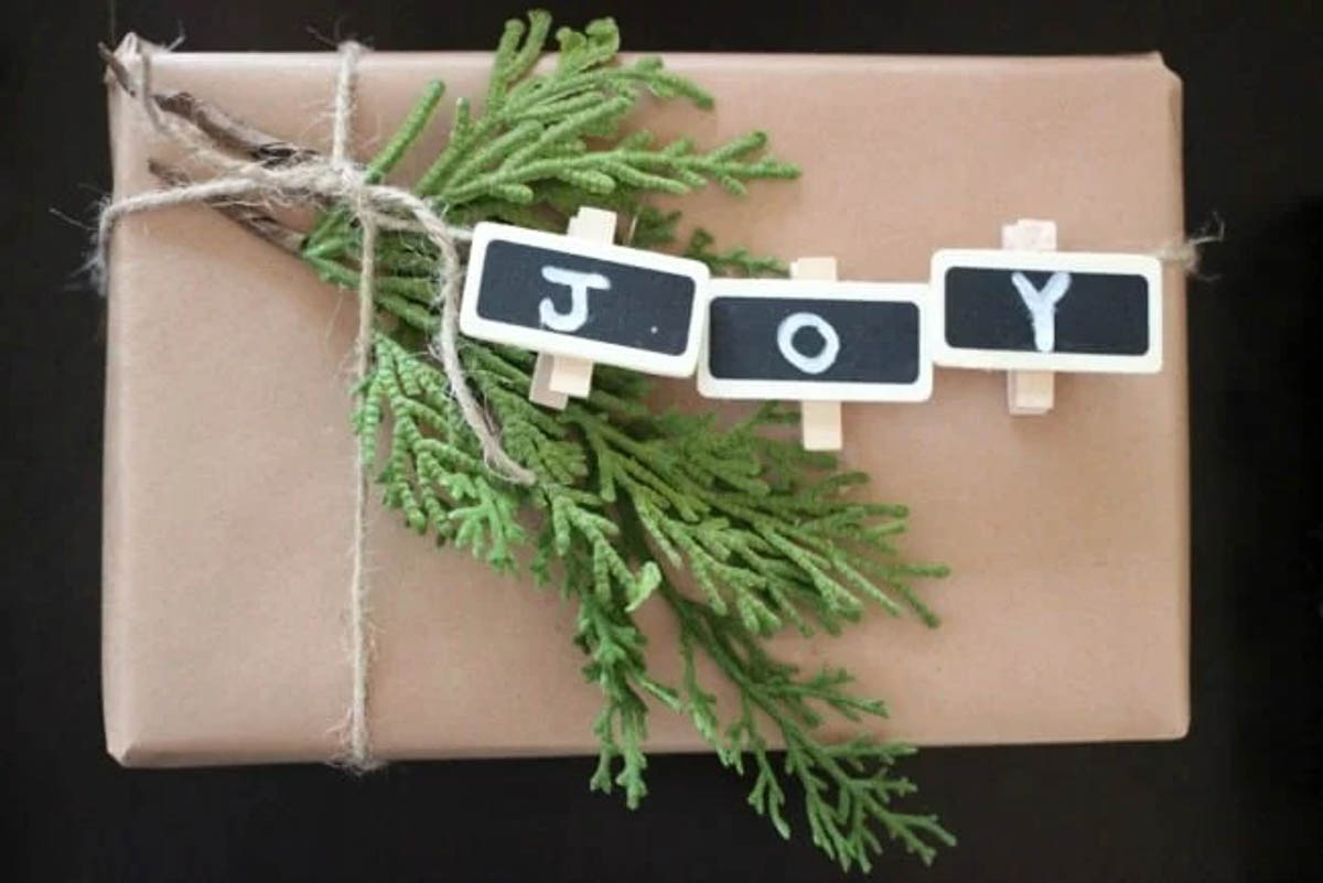 Gift wrapped with rustic gift wrapping paper and a joy sign made from clothespins