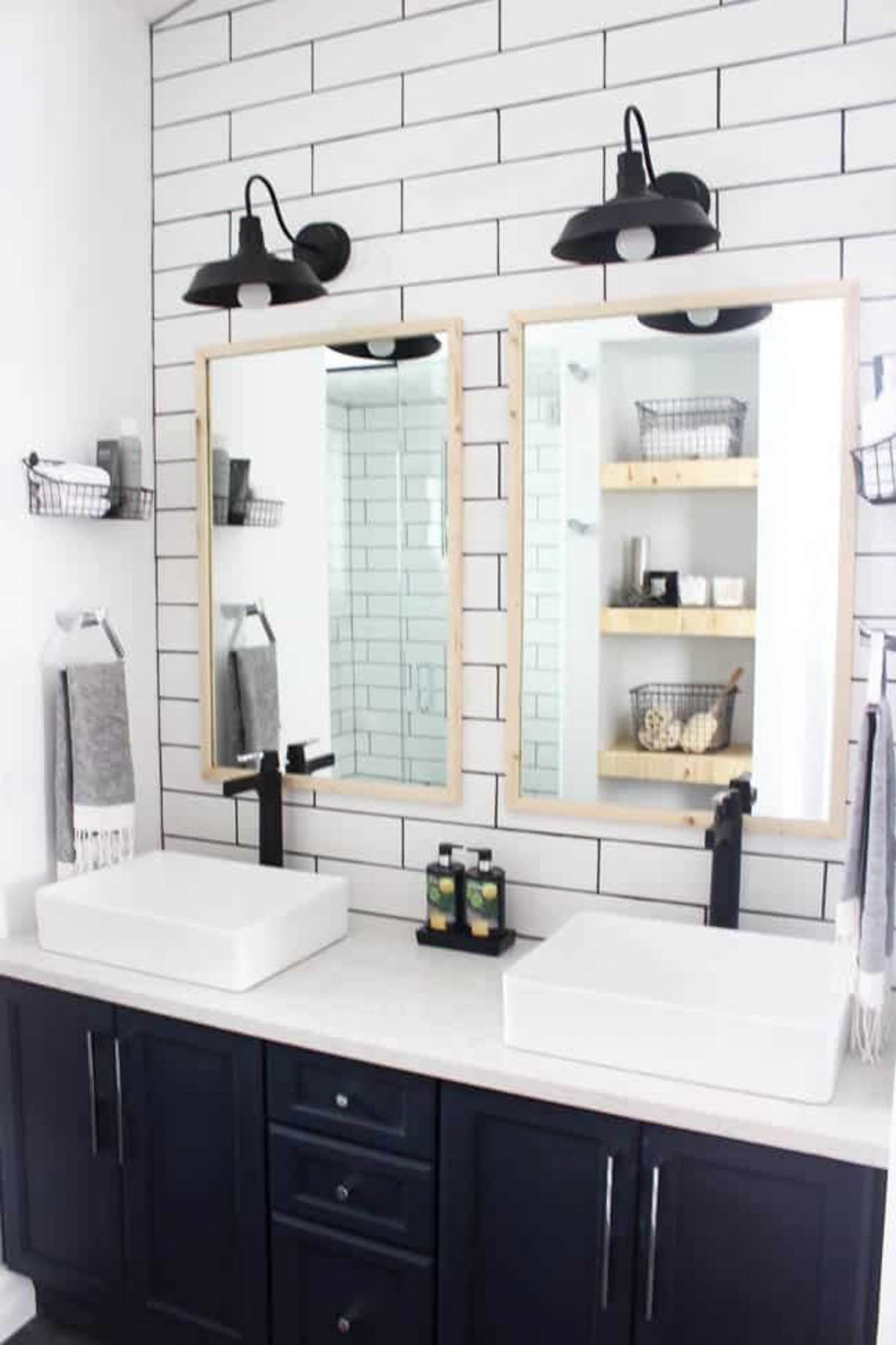 Renovated bathroom with wood-framed mirrors and subway tiles