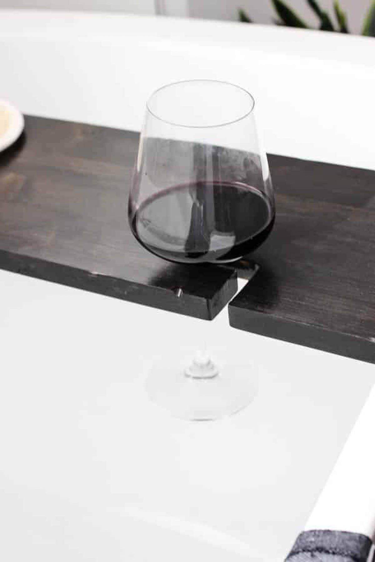 Wine glass in the holder of the bath tray with wine glass holder