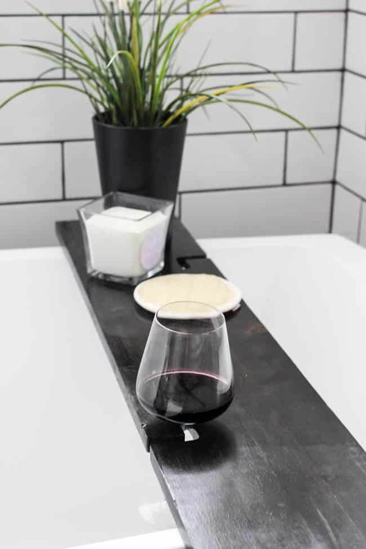 Finished bath tray on bath tub with wine glass, candle, and plant