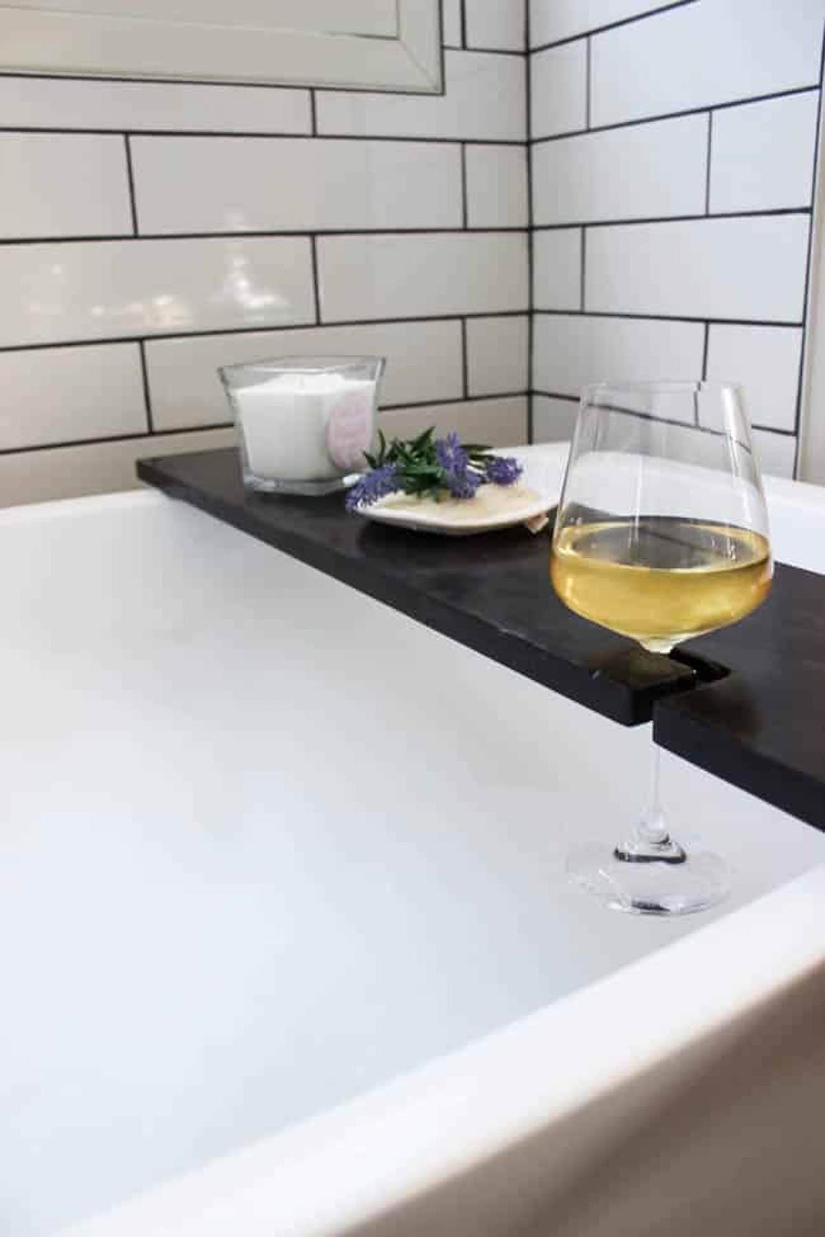 Finished DIY bath tray with wine glass holder on a bath tub