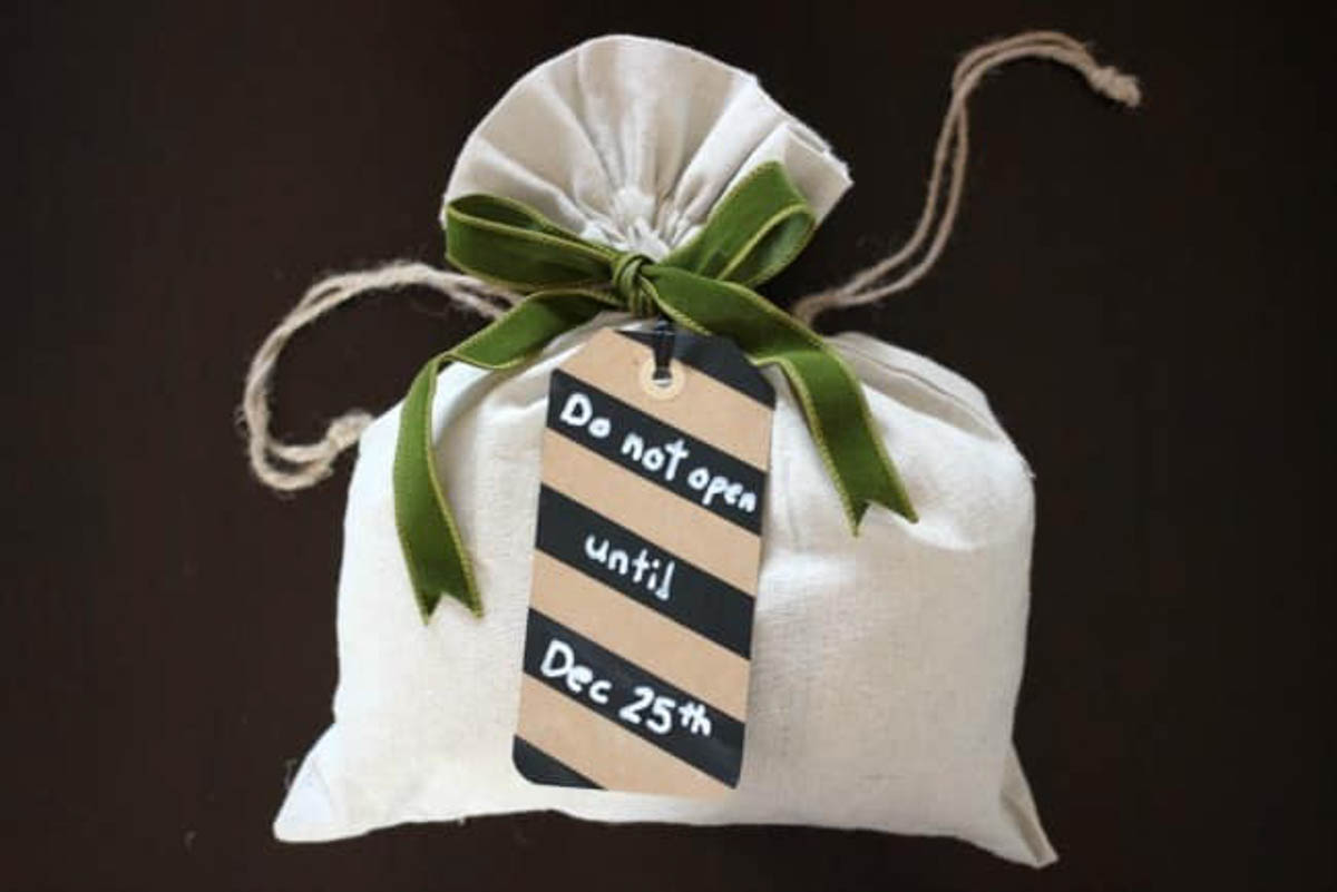 White satchel with striped tag and green bow