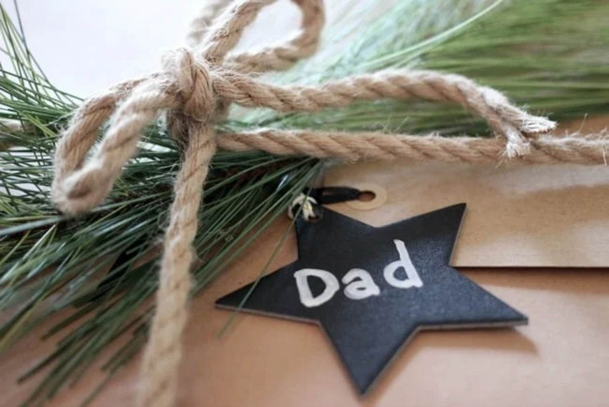 Close of rustic brown gift wrapped present with star tag, greenery, and rope bow