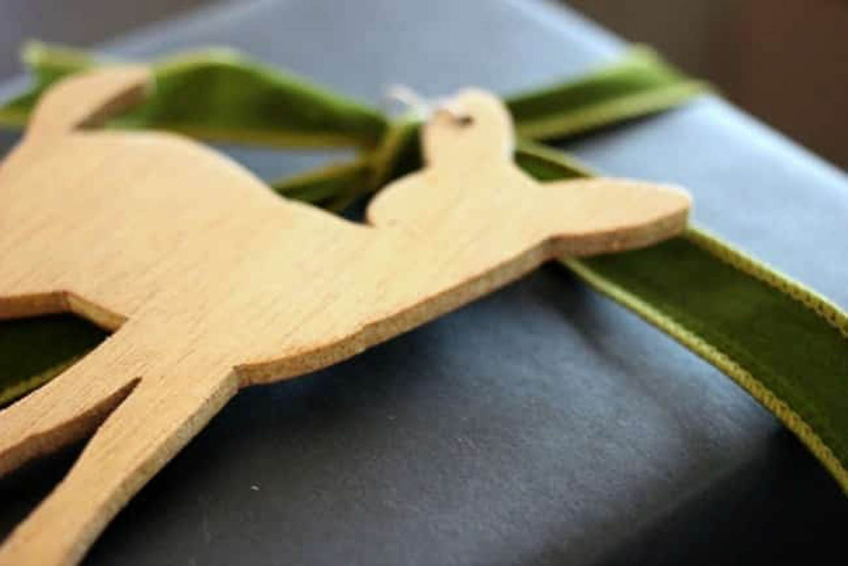 Close up of wooden deer and green bow on blue rustic gift wrapping paper