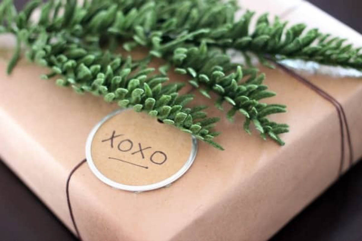 Close up of brown rustic gift wrapped present with greenery and xoxo tag