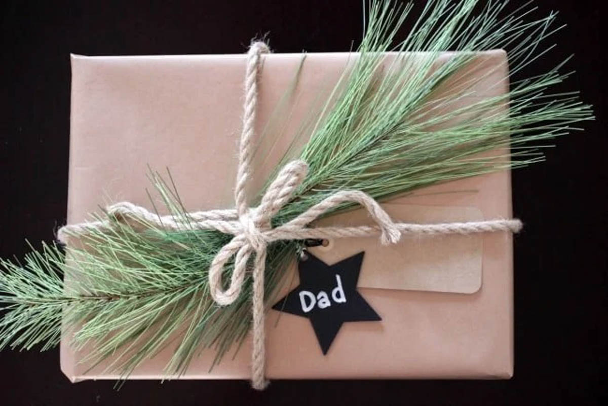 Rustic brown gift wrapped present with greenery star tag and rope bow
