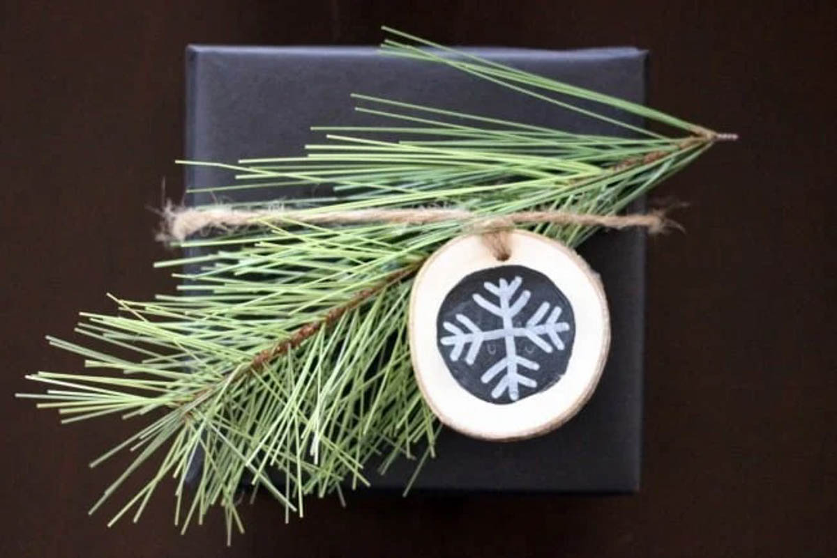 Dark blue rustic gift wrapped present with pine needles and wooden snowflake tag