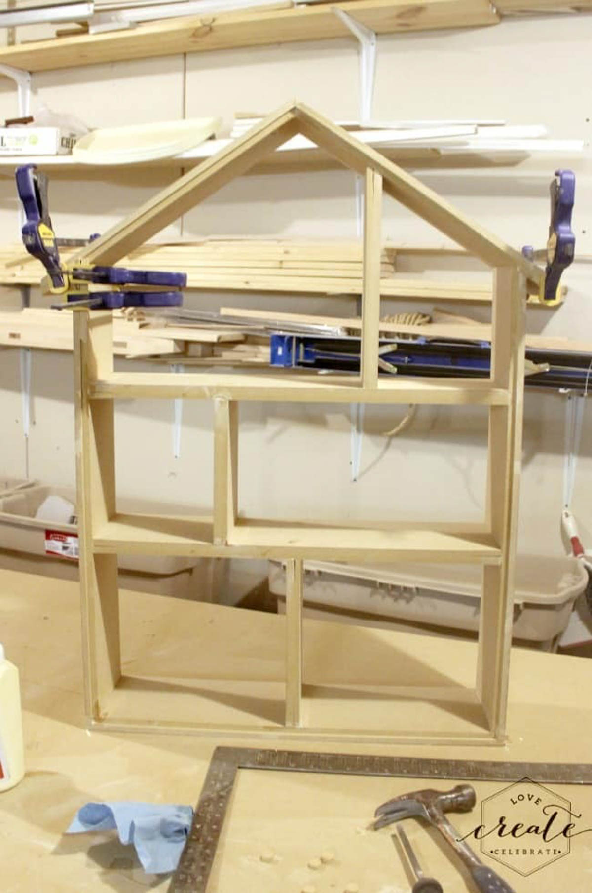 Framed house bookshelf being held together with clamps