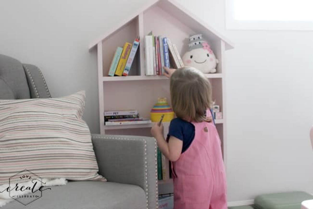 Girl picking out a book on the house bookshelf