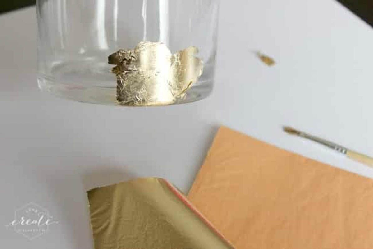 Applying the gold leaf to the adhesive piece by piece