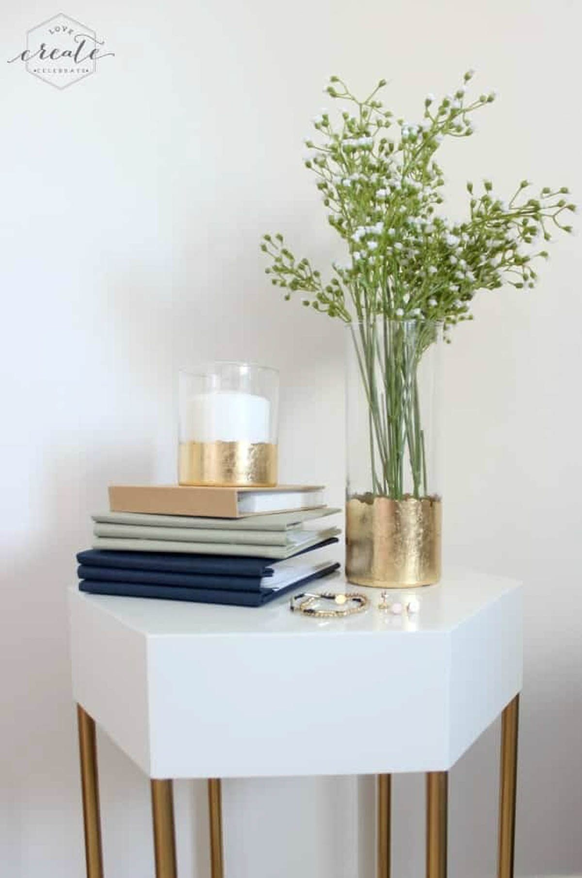Gold leaf vase on a table with photo albums and a gold leaf candle holder