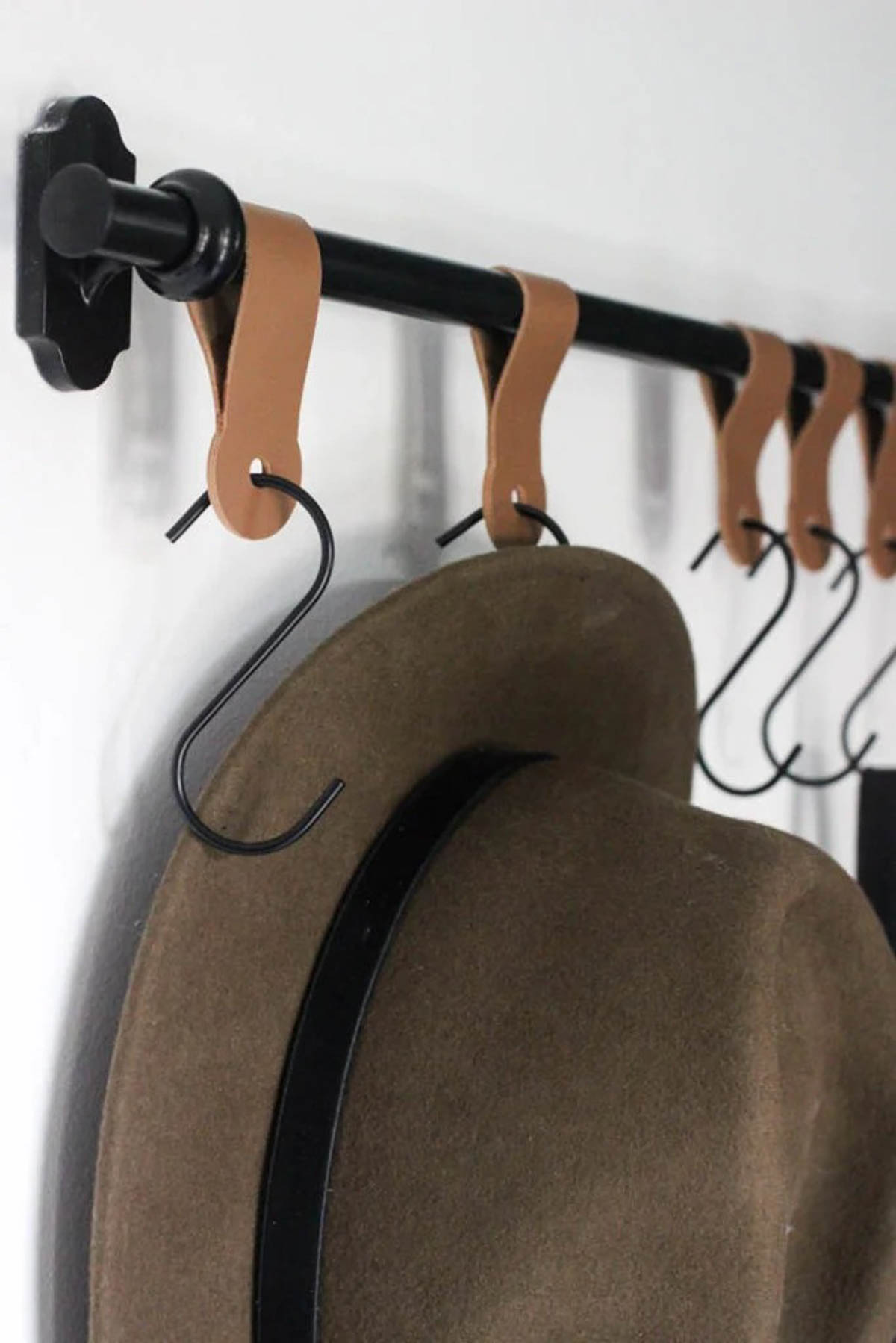 Leather straps with metal hooks holding a hat